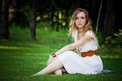 Het mooie meisje zit op het gras royalty-vrije stock afbeelding