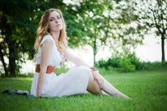 Het mooie meisje zit op het gras royalty-vrije stock fotografie