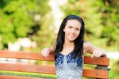 Het mooie meisje zit in park Stock Foto