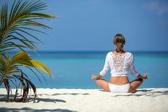 Het mooie meisje zit in stelt van een lotusbloem en mediteert op de kust de Maldiven Royalty-vrije Stock Foto's
