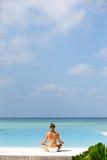 Het mooie meisje zit in stelt van een lotusbloem en mediteert op de kust de Maldiven Stock Foto's