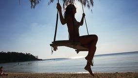 Het mooie meisje in zonnebril ontspant op de schommeling bij tropisch strand Langzame Motie 1920x1080 stock video