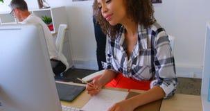 Het mooie mengen-ras vrouwelijke uitvoerende schrijven op een blocnote bij bureau in modern bureau 4k stock footage