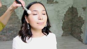 Het mooie model krijgt een professionele die make-up door een visagist Super video wordt gedaan stock video