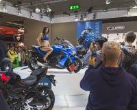Het mooie model stellen op Suzuki-motor bij EICMA 2014 in Milaan, Italië Stock Foto's
