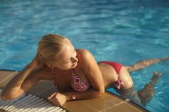 Het mooie modieuze en sexy blondemeisje in bikini stelt in zwembad stock foto
