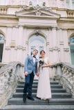 Het mooie modieuze geklede jonggehuwdepaar stellen op oude treden bij het oude Oostenrijkse paleis royalty-vrije stock foto's