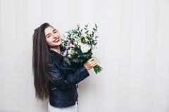 Het mooie modieuze meisje kleedde zich in leerjasje die, die boeket van bloemen houden en tegen witte muur stellen royalty-vrije stock foto