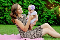 Het mooie moeder en baby spelen in een park outdoors stock foto