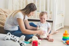 Het mooie moeder spelen op vloer met haar babyjongen bij het leven ro stock foto