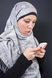 Het mooie moslimvrouw texting Stock Foto's