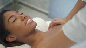 Het mooie multi-etnische vrouwelijke model krijgt de behandeling van de schoudermassage stock videobeelden