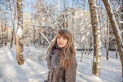 Het mooie nadenkende meisje met rode haar en sneeuwvlokken op het haar is op de achtergrond van een de winterstad op een zonnige  stock afbeelding