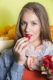 Het mooie natuurlijke donkerbruin kijken etend aardbeien Stock Foto