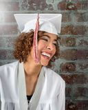Het mooie Natuurlijke glimlachen mengde rasmeisje in wit GLB en toga met rode en witte leeswijzers royalty-vrije stock afbeelding