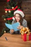 Het mooie Nieuwjaar van de meisjeslezing en Kerstmisgelukwens Stock Fotografie