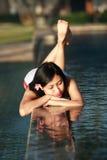 Het mooie Ontspannen van de Vrouw in een Zwembad Stock Foto