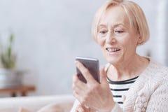 Het mooie opgewekte bejaarde texting op telefoon stock afbeelding