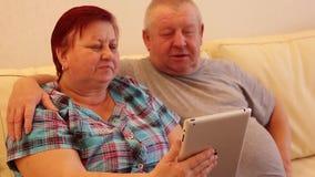 Het mooie oude paar gebruikt een digitale tablet en glimlacht zitting op laag stock footage