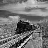 Het mooie oude stoomtrein drijven langs een brug in het platteland Concept voor reis, vervoer en retro oude stijl zwart royalty-vrije stock foto's