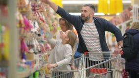 Het mooie paar en hun dochter hebben pret terwijl het doen van het winkelen in supermarkt stock video