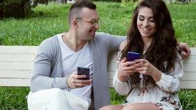 Het mooie paar gebruikt de telefoon op een bank in het park, online winkelend stock footage