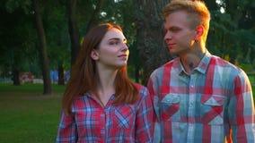 Het mooie paar hangt uit in de zomerpark en kust naar camera, mooie vibes, blije lengte openlucht stock footage