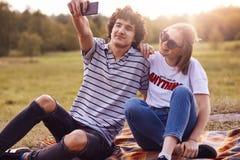 Het mooie paar heeft pret samen, zit op plaid openlucht, geniet van zonnig warm weer, stelt voor het maken selfie bij camera van  royalty-vrije stock afbeelding