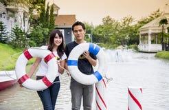 Het mooie paar houdt de het levensring op de haven Stock Foto