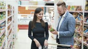 Het mooie paar kiest producten in supermarkt stock video