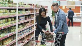 Het mooie paar kiest producten in supermarkt stock videobeelden