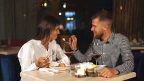 Het mooie paar in liefde zit in koffie, het drinken koffie en het eten van kaastaart De jonge vrouw voedt de haar mens stock video