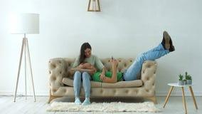 Het mooie paar ontspannen op de bank thuis stock footage