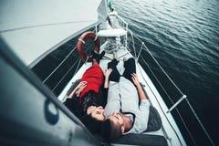 Het mooie paar openlucht ontspannen op het jacht Stock Foto
