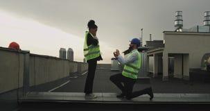 Het mooie paar van architecten multi-etnisch op het dak van de bouwwerfmens een voorstel voor zijn vrouw doet zij stock video