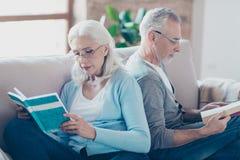 Het mooie paar van oude vrouw en de echtgenoot lezen boek met glas royalty-vrije stock foto