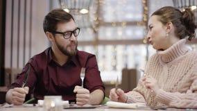 Het mooie paar wacht op maaltijd door lijst in de vorken en de messen van de restaurantholding stock video