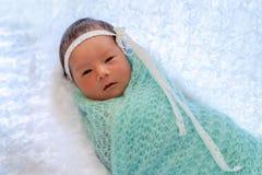 Het mooie pasgeboren meisje bepaalt op witte deken omhoog warpping met lichtgroene stof, 6 dagen oude, zachte nadruk royalty-vrije stock fotografie