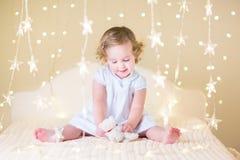 Het mooie peutermeisje spelen op een bed tussen warme zachte Kerstmis l Stock Foto's