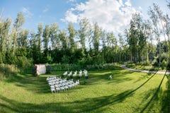 Het mooie plaatsen voor in openlucht huwelijksceremonie die op bruid en bruidegom en gasten wachten Witte die stoelen worden verf Royalty-vrije Stock Afbeeldingen