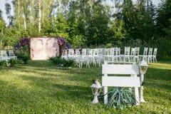 Het mooie plaatsen voor in openlucht huwelijksceremonie die op bruid en bruidegom en gasten wachten Witte die stoelen worden verf Stock Fotografie