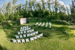 Het mooie plaatsen voor in openlucht huwelijksceremonie die op bruid en bruidegom en gasten wachten Witte die stoelen worden verf Stock Afbeeldingen