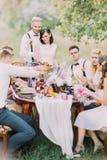 Het mooie portret van de jonggehuwden die hun huwelijk snijden koekt en hun gasten Lijst het plaatsen van het huwelijk royalty-vrije stock foto's