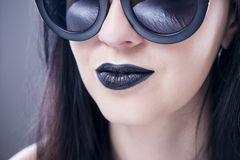 Het mooie portret van de vrouwenmannequin in zonnebril met zwarte lippen en oorringen Het creatieve kapsel en maakt omhoog Stock Afbeeldingen