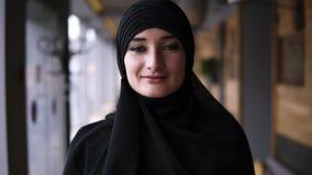 Het mooie portret van een jong moslimmeisje in zwarte hijab stelt voor de camera, lettend op bij camera Godsdienstig Concept stock footage