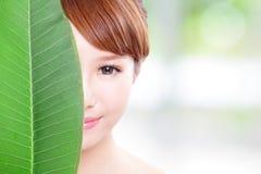 Het mooie portret van het vrouwengezicht met groen blad stock afbeeldingen