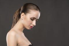 Het mooie portret van meisjes naakte schouders op een grijze achtergrond Stock Foto's
