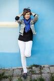 Het mooie positieve vrouw stellen voor de blauwe muur Stock Afbeeldingen