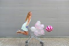 Het mooie rollende boodschappenwagentje van het blondemeisje met kleurenballons Royalty-vrije Stock Fotografie