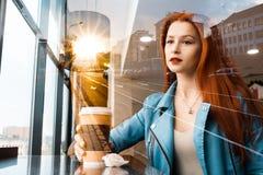Het mooie romantische meisje drinkt koffie in een koffie roodharige vrouwenzitting dichtbij het venster tegen de achtergrond van  royalty-vrije stock afbeelding